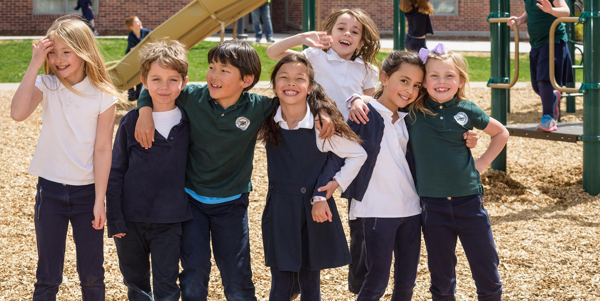 Lower Schools laugh and embrace on playground.