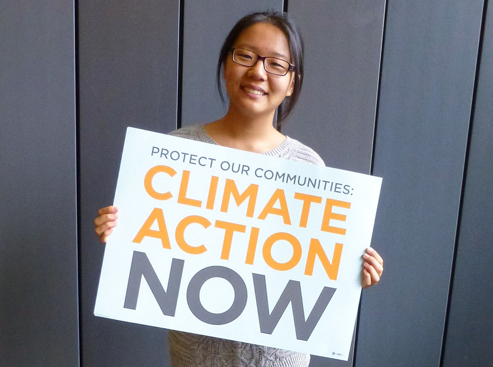 Claire Wang holding climate action now sign